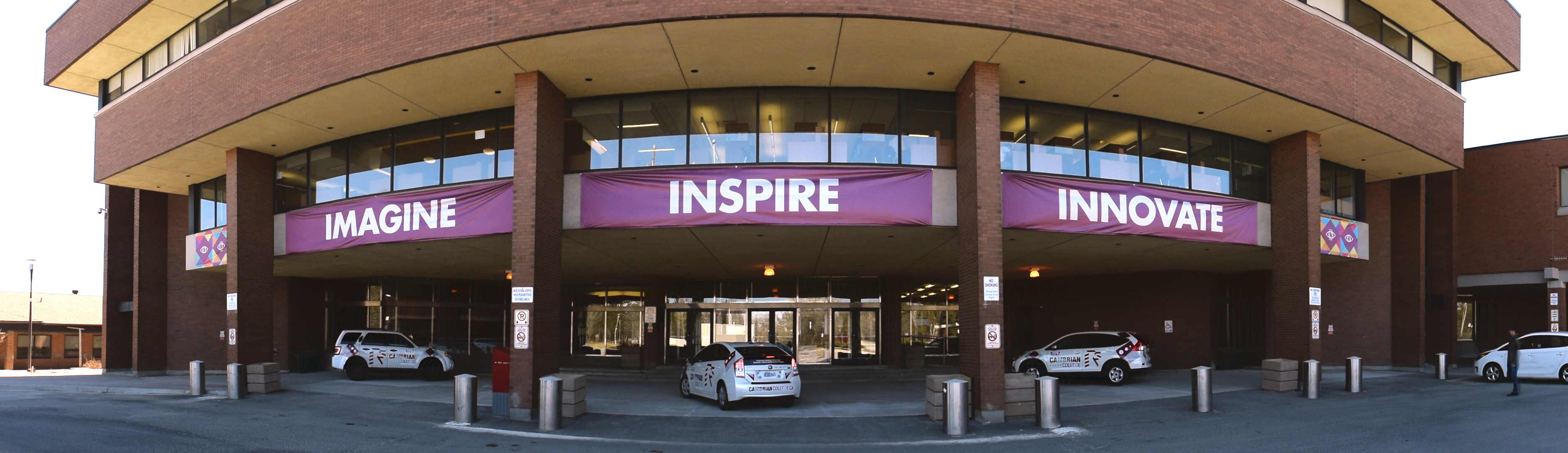 """A front view of Cambrian College with the words """"Imagine,"""" """"Inspire,"""" Innovate"""" displayed"""