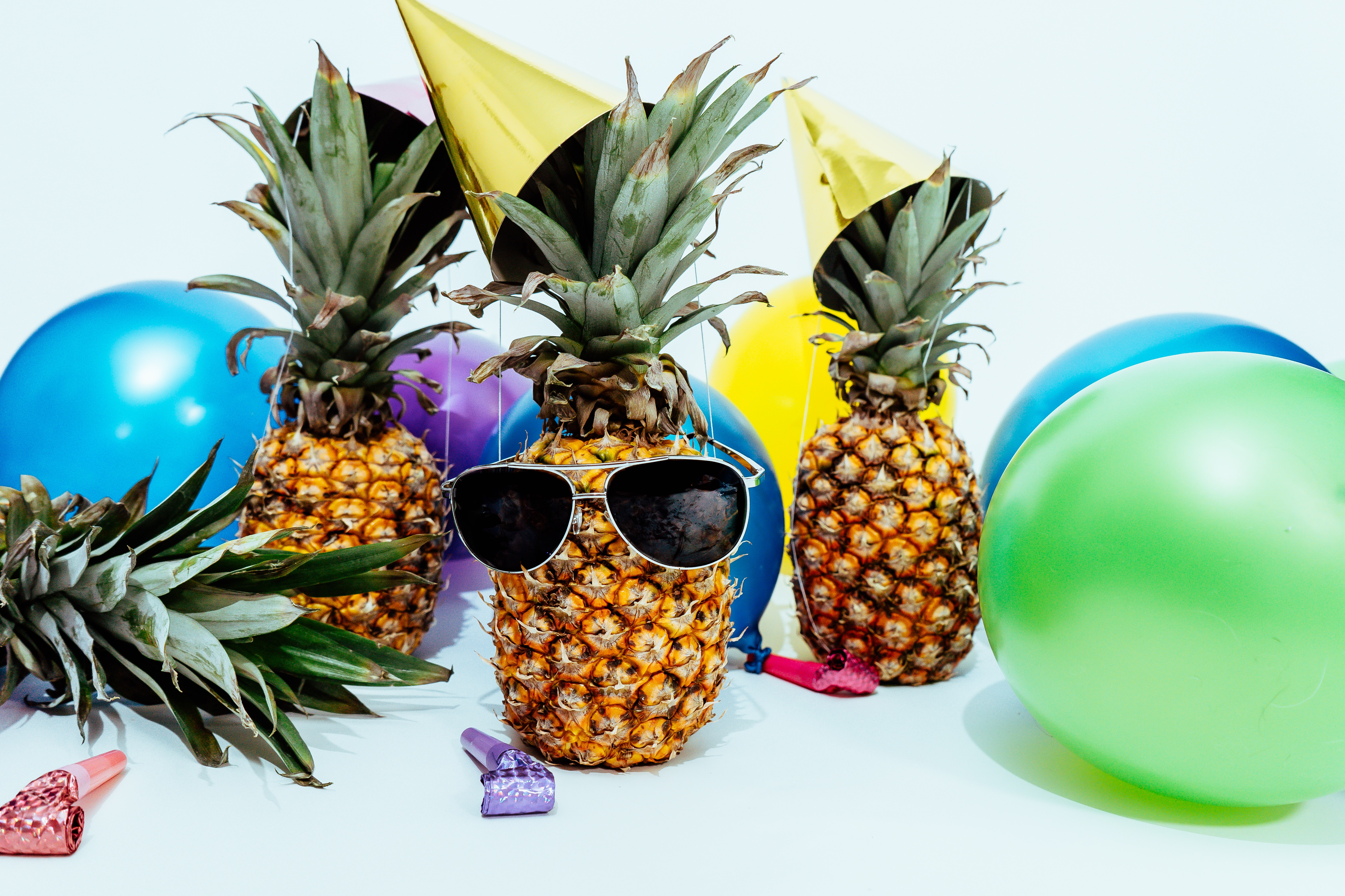 Pineapple with sunglasses, balloons, party hats